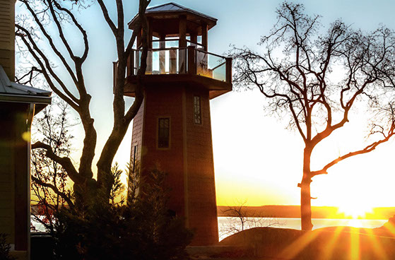 A lookout tower shaped like a lighthouse, shines in the sunset sitting on a property above Grand Lake.